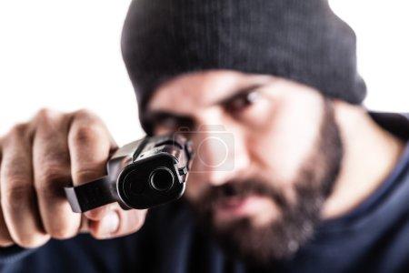 Photo pour Un criminel barbu pointant un pistolet et coiffé d'un chapeau bonnet isolent sur blanc - image libre de droit