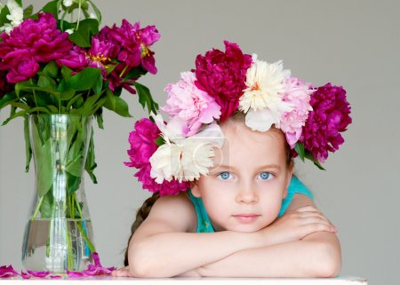 Adorable little girl with wreath from peony flowers