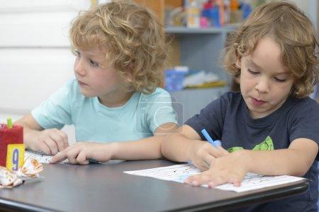 Photo pour Deux frères peignent à la maternelle - image libre de droit