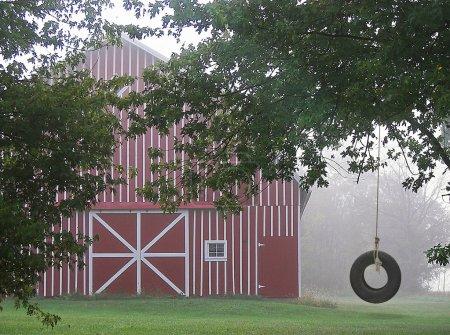 Photo pour Grange rouge dans la brume avec une vieille balançoire à pneus . - image libre de droit