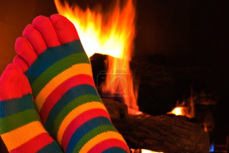 Striped toe socks by fireplace