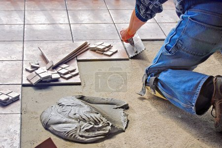 Photo for Man laying ceramic tile flooring with a pile of mud. - Royalty Free Image