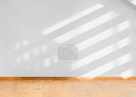 Photo pour Salle vide avec plancher de bois et de la diagonale des ombres sur le mur blanc - image libre de droit