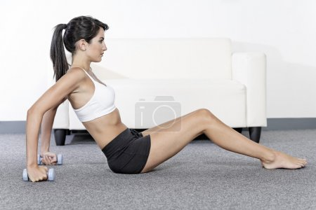 Photo for Beautiful young woman training with weights at home - Royalty Free Image