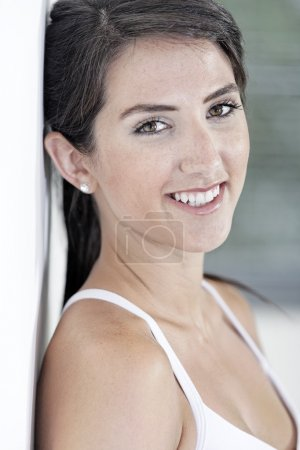 Portrait of woman resting against wall