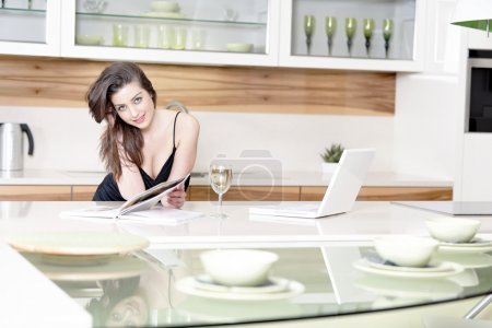 Photo for Attractive young woman using a laptop while enjoying a glass of wine in the kitchen - Royalty Free Image