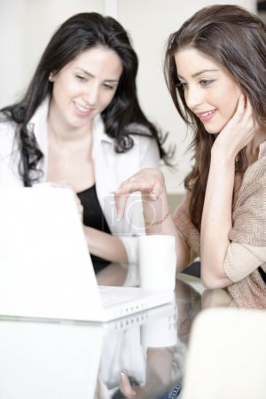 Two friends using a laptop