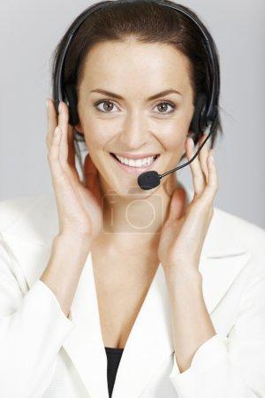 Photo pour Joyeux centre d'appels dame avec casque téléphonique - image libre de droit