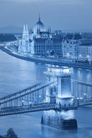 Photo pour Image tonique du parlement hongrois et du pont de la chaîne à Budapest pendant l'heure bleue crépusculaire . - image libre de droit