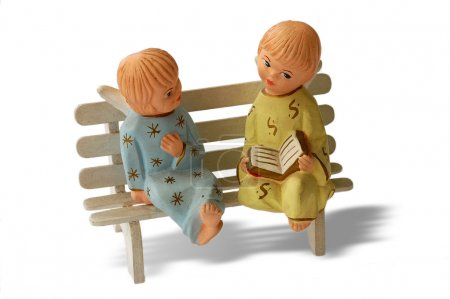 Photo for Two ceramic little angels sitting on a bench on white background - Royalty Free Image
