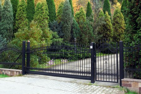 Black modern gate and green garden