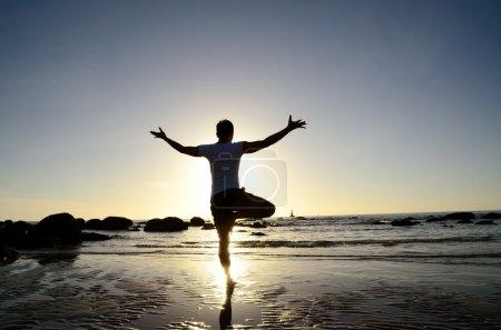 Man act yoga on the beach