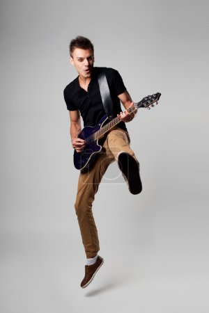 Photo for Rockstar men jumping with guitar while playing - Royalty Free Image