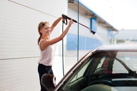 Pretty woman washing the car