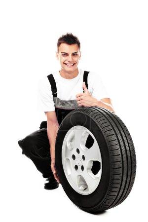 Auto mechanic holding car wheel