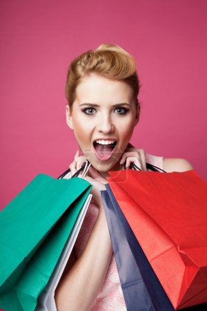 Photo for Happy woman with shopping bags screaming. Isolated on pink - Royalty Free Image