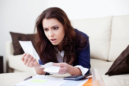 Desperate young woman looking at bills