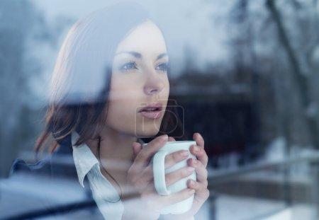 Photo pour Jeune femme buvant café regardant par la fenêtre - image libre de droit