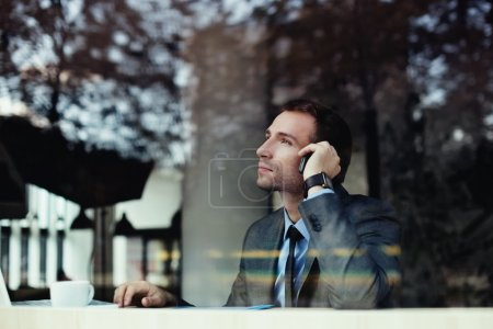 Businessman talking on phone in coffee shop