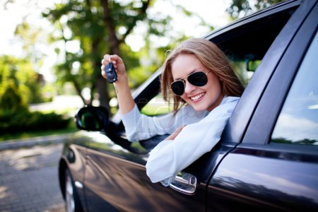 Young woman shows the keys to her new car...