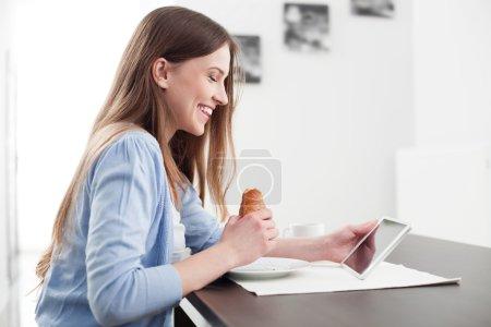 Photo pour Femme manger le petit déjeuner et lire les nouvelles sur tablette numérique - image libre de droit