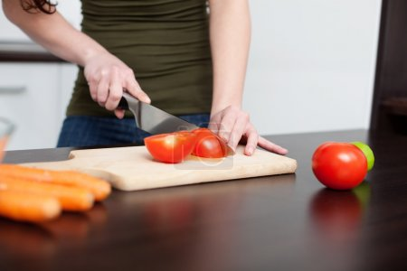 Photo for Food preparation. Woman cutting red tomato in the kitchen. - Royalty Free Image