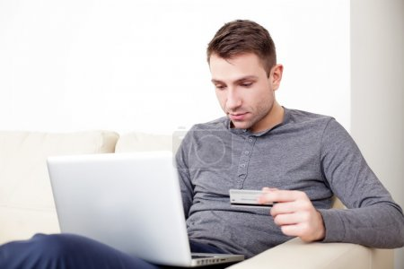 Handsome man holding credit card and using his laptop