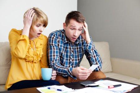 Shocked couple paying bills.
