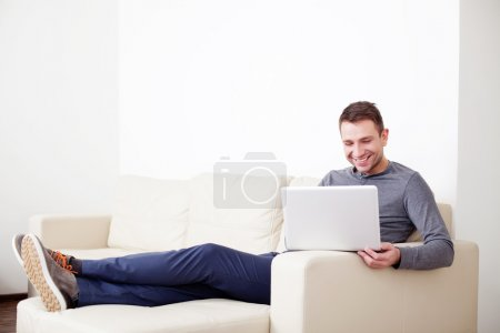 Man sitting on sofa with digital tablet