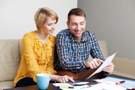 Happy couple calculating bills