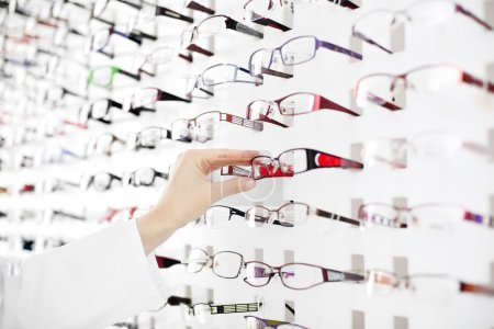 Photo for Optician suggest glasses. Closeup showing many eyeglasses in background. - Royalty Free Image