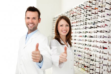 Two happy optician, optometrist showing thumbs up