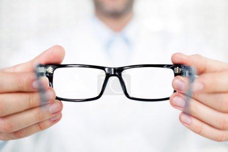 Closeup of optometrist, optician giving glasses