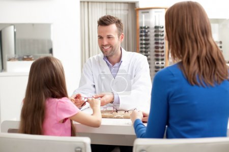 Photo pour Opticienne, optométriste donnant des lunettes à essayer pour une jeune fille visitant un magasin d'optique avec sa mère - image libre de droit