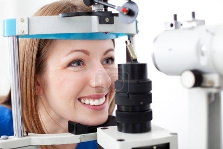 Photo pour Jeune femme se fait examiner les yeux par optométris - image libre de droit