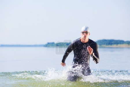 Triathlete running out of the water on triathlon r...