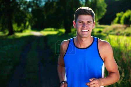 Happy young man running in countryside