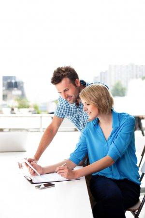 Photo pour Jeune couple travaillant ensemble sur une tablette numérique au bureau. notions de travail d'équipe. - image libre de droit