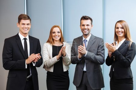 Happy business people clapping their hands