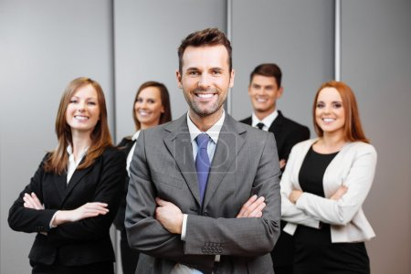 Photo for Team leader stands with coworkers in background - Royalty Free Image