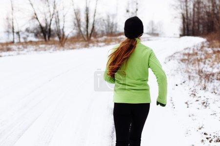 Woman running in winter snow
