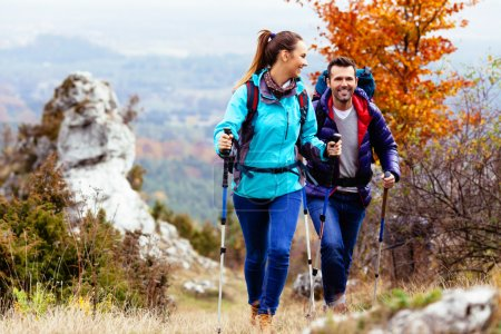 Photo pour Femme et homme randonnée dans les montagnes avec des sacs à dos - image libre de droit