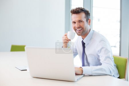 Photo for Businessman working on laptop and drinking on coffee break - Royalty Free Image