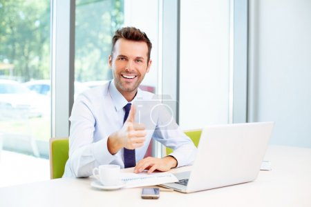 Foto de Businessman showing thumbs up in the office - Imagen libre de derechos