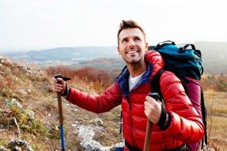Smiling hiker holding poles