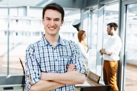 Photo pour Portrait d'un jeune professionnel heureux au bureau regardant la caméra - image libre de droit