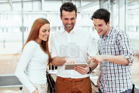 Smiling professionals looking at tablet
