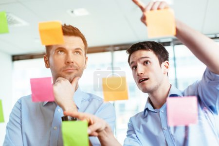 Businessmen discussing ideas on sticky notes