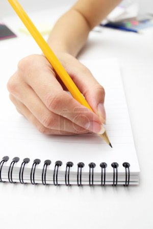 Photo for Woman's hand writing in a notebook with a pen - Royalty Free Image