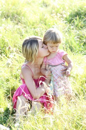 Photo for Young mother and her little daughter on the grass outdoors - Royalty Free Image
